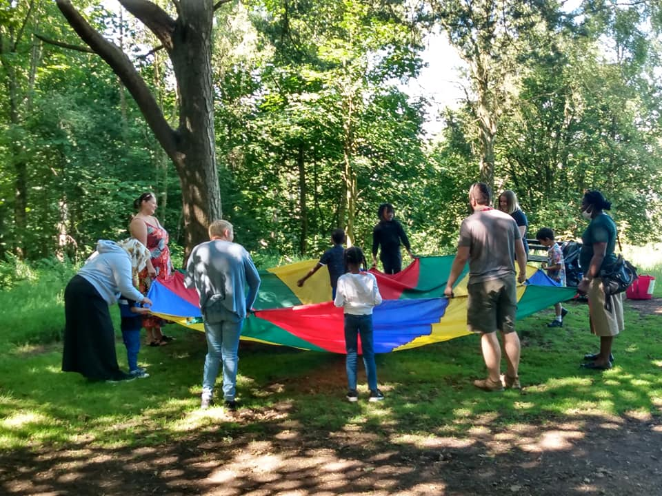 group of people in a circle holding a parachute