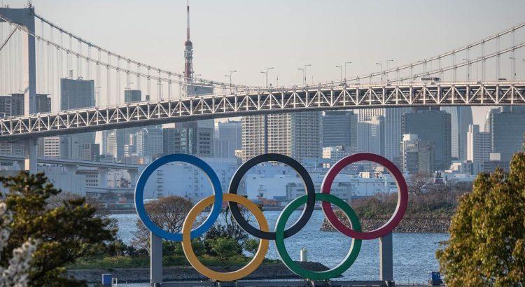 Imagem dos aros olímpicos com Tóquio ao fundo durante o dia.