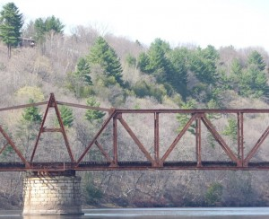 The railroad swing bridge in spring, with leafless hardwoods and dark green White pines on the bluff behind it.
