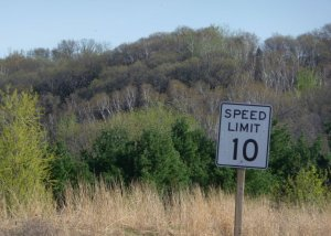 Speed limit 10 mph sign with wooded bluff in the background