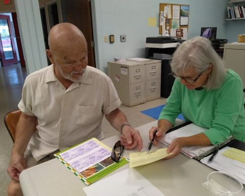 Franz Burnet-Gocht receives his farmers market coupons from Marion Quinn-Jowett; photo by Sheila Velazquez.