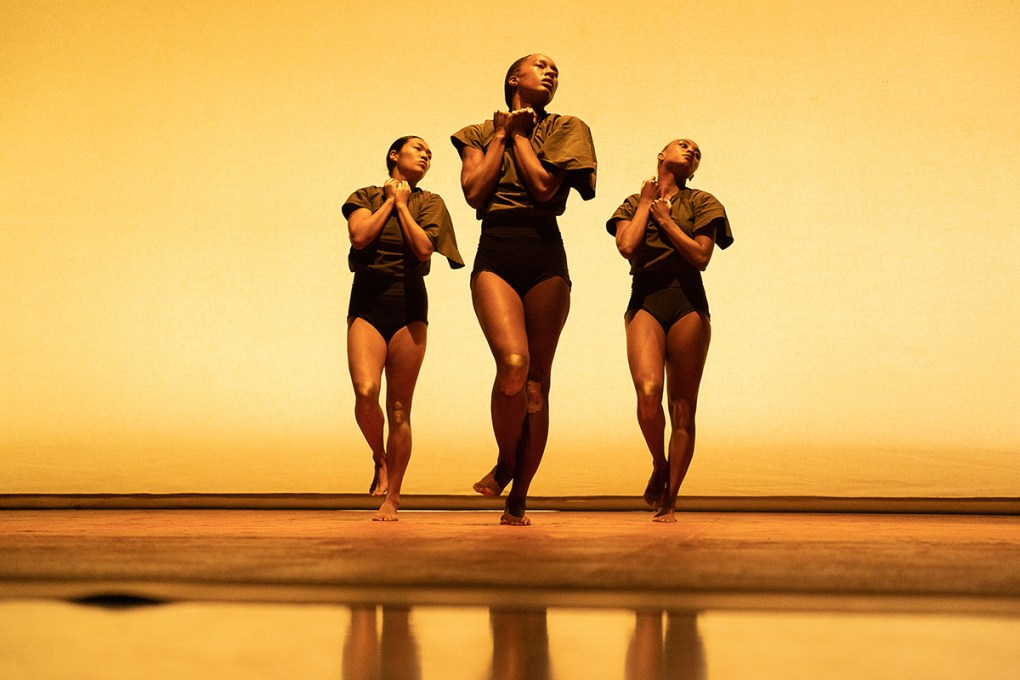 """Photo of three female dancers with their hands clasped over their hearts: Keerati Jinakunwiphat, Catherine Ellis Kirk, and Marcella Lewis of A.I.M in Andrea Miller's """"state""""; photo by Hayim Heron."""