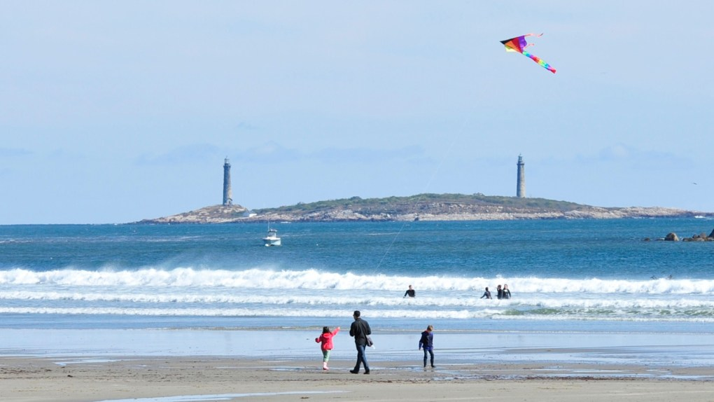 Photo of family flying a kite on the beach with an island in the background that hosts a lighthouse on each end: Good Harbor Beach Thacher Island — A view of Thacher Island, the only multiple lighthouses in operation on the U.S. coast, from the shore of Good Harbor Beach; photo courtesy of Discover Gloucester.