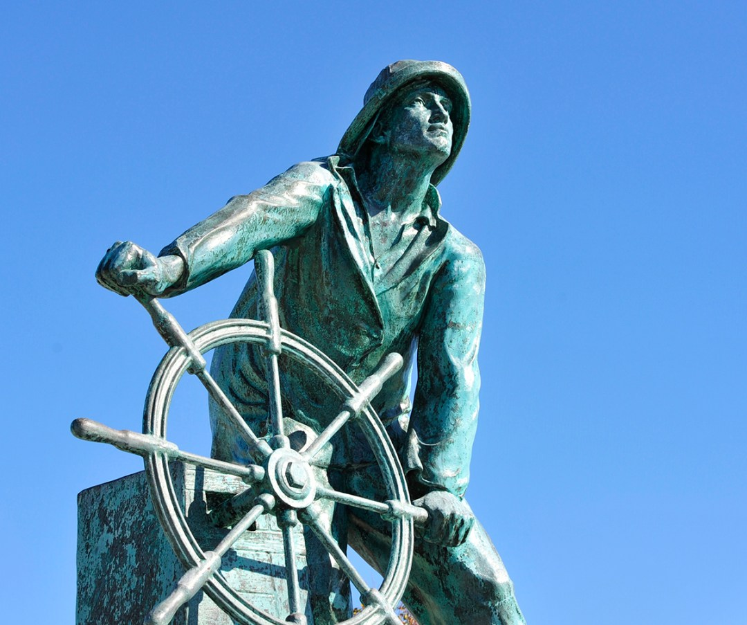 Photo of famous outdoor sculpture of fisherman holding the wheel of a ship and looking off in the distance: The Man at the Wheel statue is part of Gloucester's Fishermen's Memorial. Artist Leonard Craske modeled it on a local fisherman in 1925; photo courtesy of Discover Gloucester.