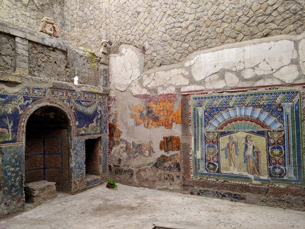 The sea god Neptune and his wife, Amphitrite, are the subjects of the colorful mosaics at right. On the left is a shrine to nymphs made of seashells, lava foam, and tile. A marble theatrical mask looks down on the home, which belonged to a wealthy family.