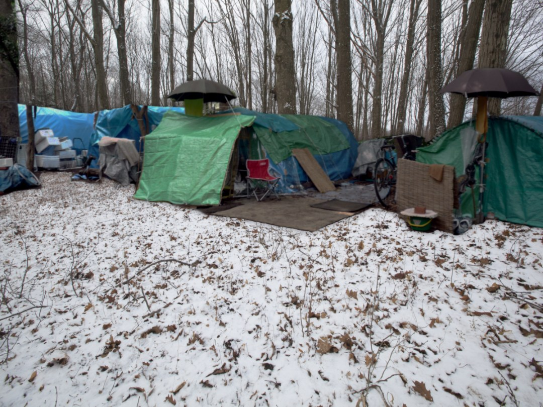 Photo of a homeless encampment in a snow-covered clearing in a forest