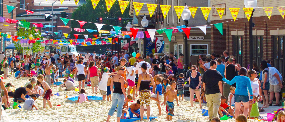 Photo of people and families playing in the sand at the Eagle Street Beach Party that takes place in downtown North Adams each year.