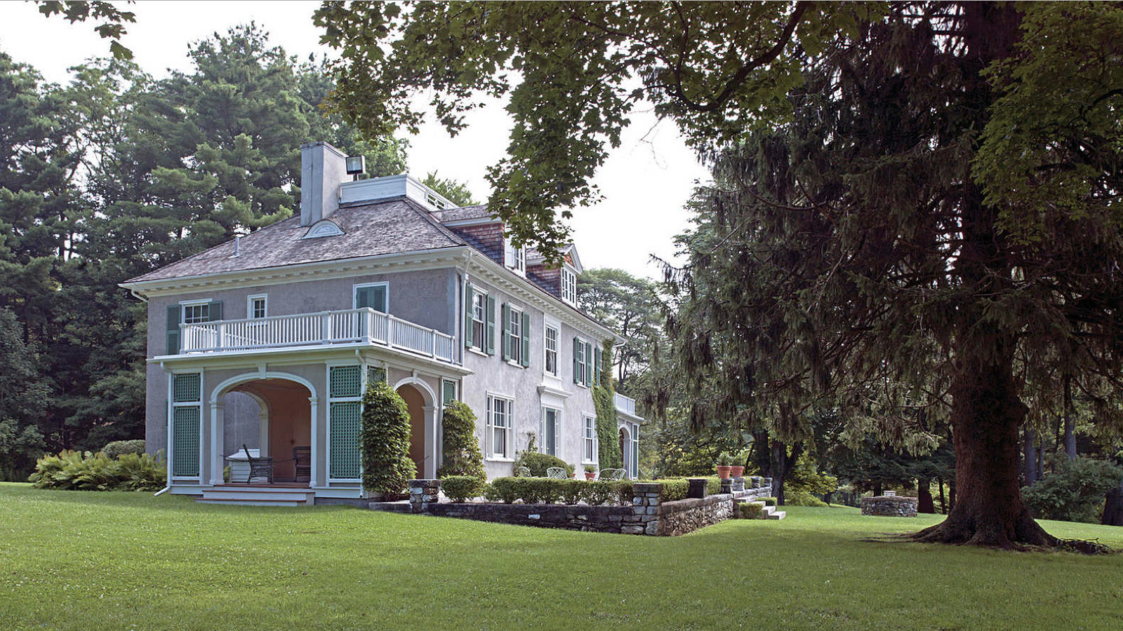 photo of Chester's mansion, taken on a sunny day in summer, surrounded by immaculately kept lawn, gardens, and towering evergreen trees.