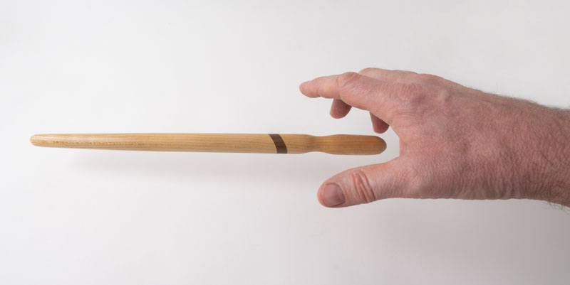 Hand reaching for a spirtle, or spurtle, in birch and walnut