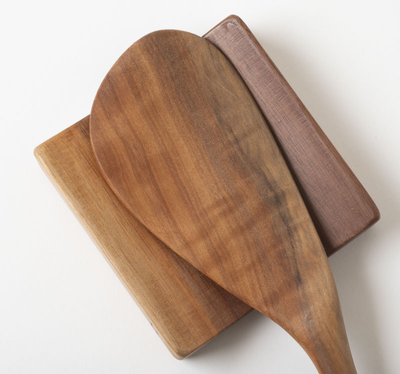 Paddle spatula resting on a spoon rest, in cherry