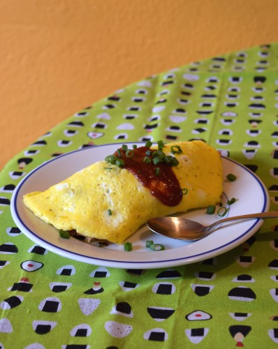 Egg omelet wrapped around fried rice with ketchup on top = omurice (omelet rice)