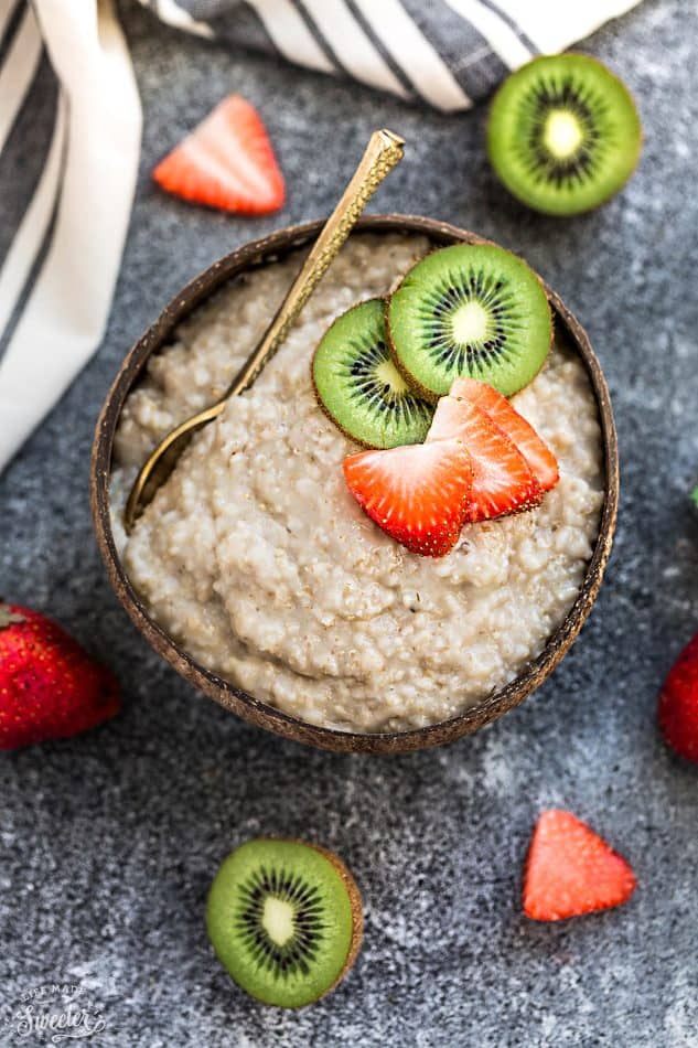 Bowl of steel cut oats topped with sliced of kiwi and strawberries.