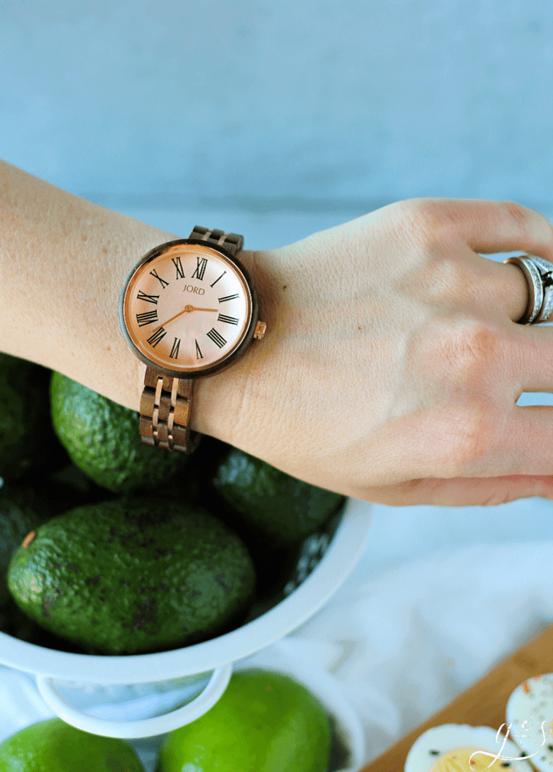 A woman's wrist adorned with a Vintage Rose and Walnut JORD watch.
