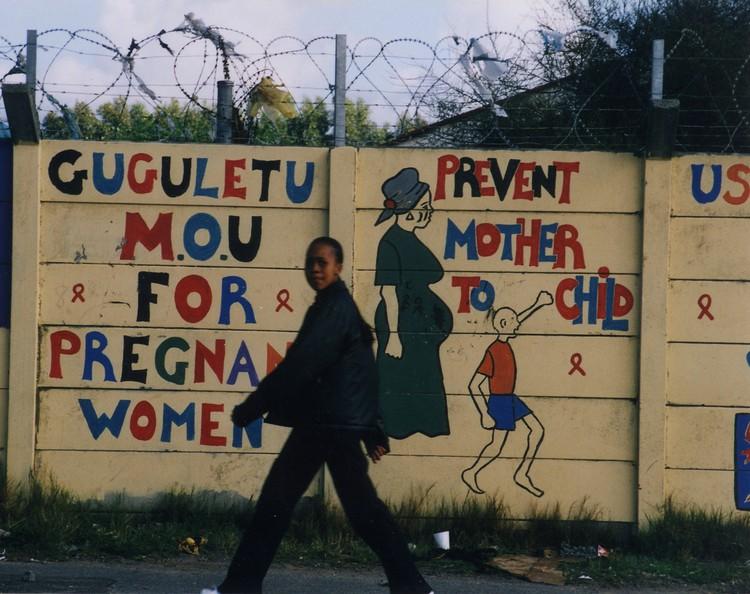 Photo of woman walking past PMTCT graffiti