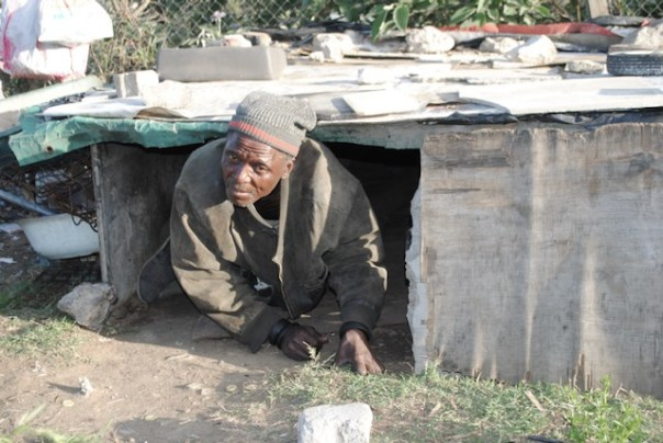 Photo of a man climbing out of a hovel