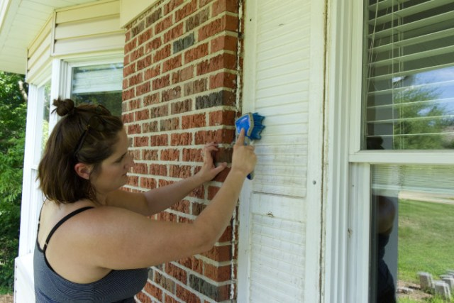 Cleaning porch shutters that were found under the original porch shutters and removing wasp nests