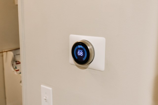 Google Nest Learning Thermostat installed on wall in entryway displaying 68 degrees Fahrenheit