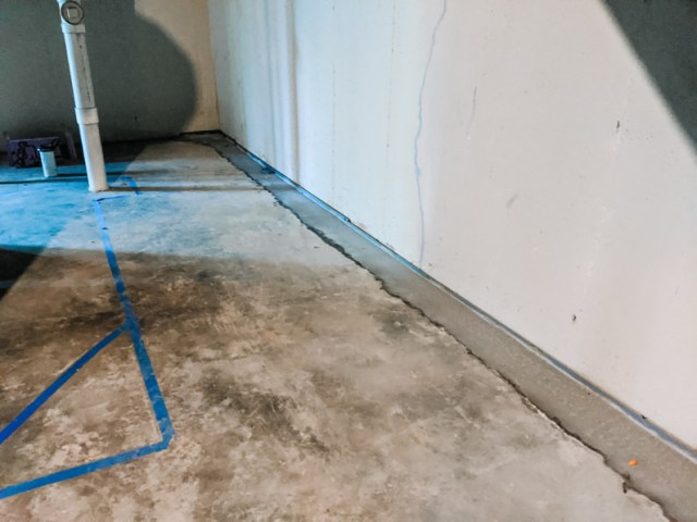 Patched concrete over drain system trench