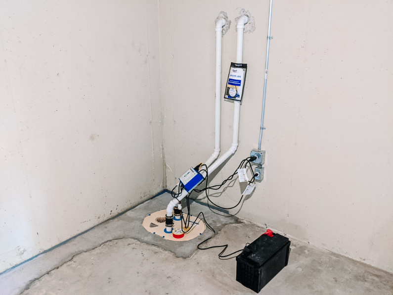 Sump pit and pump installed with drain pipes drilled into wall