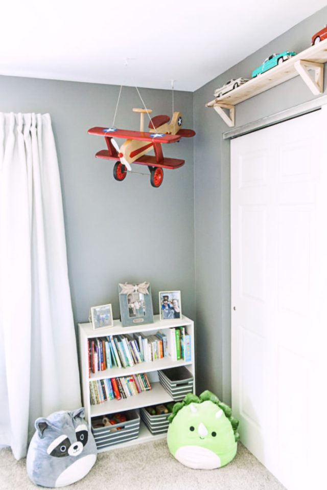 Hanging plane above bookshelf in toddler bedroom