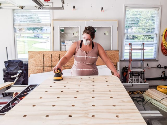 Sanding the pegboard with an orbital sander