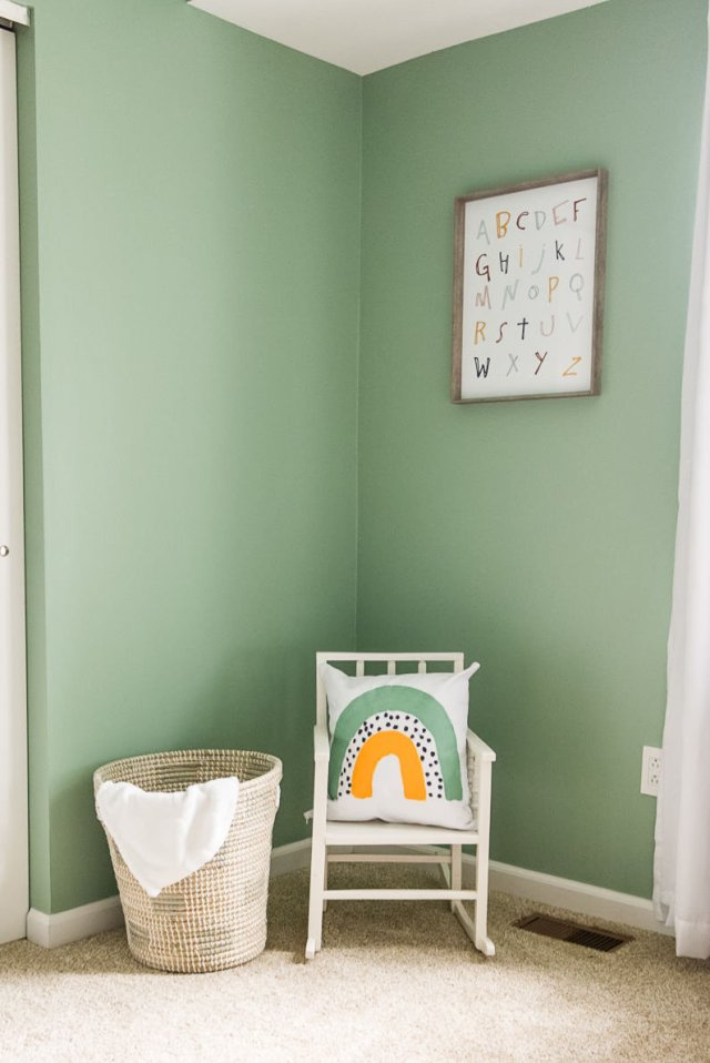 Child sized rocking chair next to basket with DIY fabric painted pillow with rainbow, alphabet wall art print
