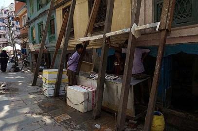 Selling fish under a broken building