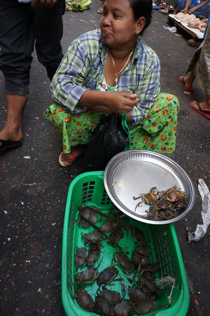 Smiling lady selling crabs in a Yangon market