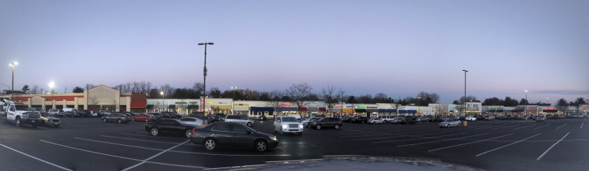 Panoramic photo of Briggs Chaney Plaza. The parking lot is full and nearly all the stores have tenants.