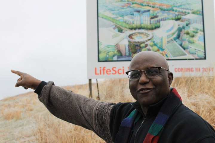 "Photo of Jewru Bandeh smiling in front of large sign that reads, ""LifeSci Village: coming in 2017"""