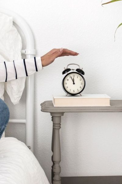 woman sitting on a bed with arm stretched out, hand hovering over black alarm clock