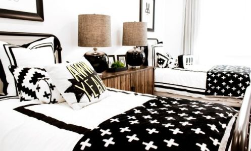 Two twin beds with black and white bedding set up for kids