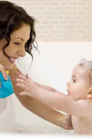 baby reaching for bath toy mom is holding