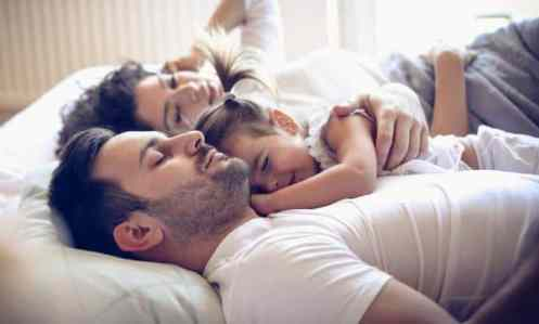 mother, dad and toddler of big family sleeping