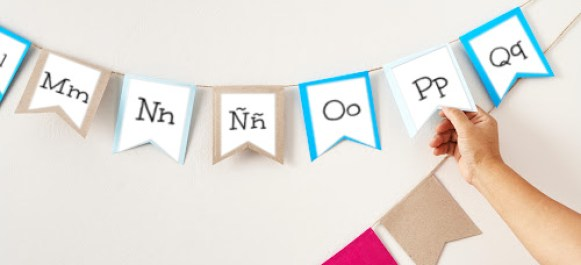 Spanish alphabet banner hanging on wall with hand