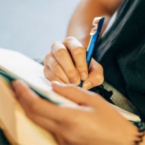 person writing in a notebook with pen