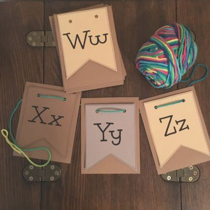 alphabet cards on wood table with yarn through holes on top