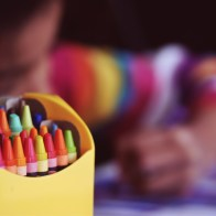 box of crayons and child with striped shirt coloring