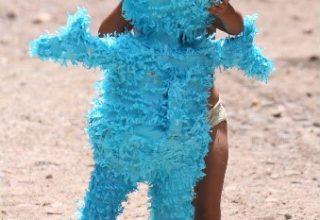 Niño jugando con un peluche azul durante el evento del día del niño
