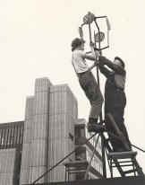 GSA Archives photograph of workmen working on the iron roof finial at the top of the Eastern wing of the Mackintosh Building (Archive reference: GSAA/P/7/94)