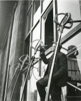 GSA Archives photograph of workman repairing a window bracket on front facade of the Mackintosh Building (Archive reference: GSAA/P/7/99)