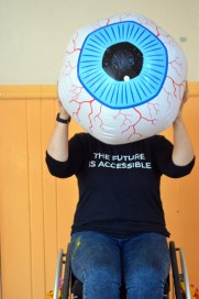 A Very Queer Nazi Faust participant holding a giant eyeball with the words 'The Future is Accessible' on her shirt. Photo by Ann Nicholls.