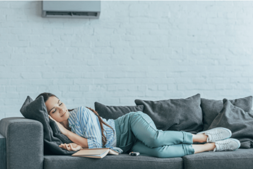 woman lying on couch under air conditioner