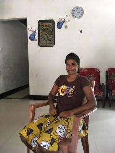 Anusha sits in a chair at her parents' home.