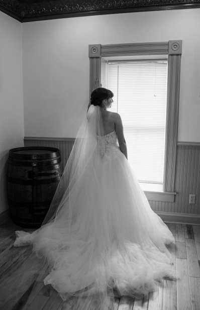 Bride in a tulle wedding dress standing by a window facing outwards in Reeder's Alley in Helena, Montana.