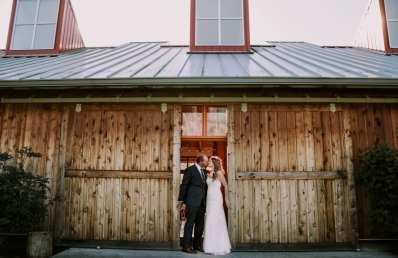 North Bend Bride and Groom kissing between brown rustic barn doors at Meadowbrook Farm