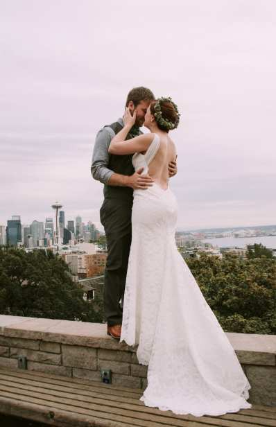 Bride and groom on the wall at Kerry Park in Seattle, with the Space Needle in the background.