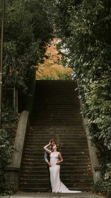 Seattle Wedding Couple on the steps near Kerry Park embracing. Bride has a lace dress and hops flower crown.