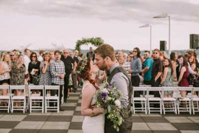 Bride and groom kissing at the end of the aisle after their rooftop wedding ceremony at Bell Harbor in Seattle. Guests are in the background and bride is holding a hops bouquet and wearing a hops crown