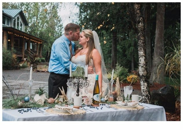 Winter Wedding at the Lookout Lodge in Snohomish bride and groom near tablescape, gold, green, brown, navy blue, cocoa mug, frost, eucalyptus, wine, antlers, pinecones